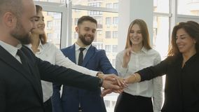 Office workers, three young women and two young men lined up in a semi-circle standing near the panoramic window of the. Office and came to an agreement and stock video