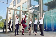 Office workers throw paper up against the background of a multi-storey glass office building. Group of young people. Five are hap. Py about the successful royalty free stock images