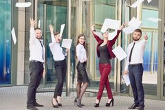 Office workers throw paper up against the background of a multi-storey glass office building. Group of young people. Five are hap. Py about the successful royalty free stock photos