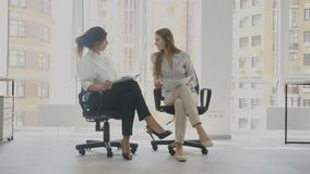 Office workers, two women sitting on chairs talking, one of the women tells about the work of another woman. 4k stock video footage