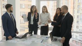 Office workers, two young managers of the firm want to conclude a joint contract, one of them with his young team shows. All the advantages of their transaction stock video