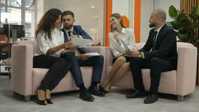 Office workers two young men and two young women, men sitting on the sofas discuss important documents of the firm, and. The girls are extraordinarily listening stock footage