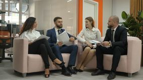 Office workers two young men and two young women, one of the men sitting on the couches, expresses her opinion about the. Documents of the firm, and the girls stock video