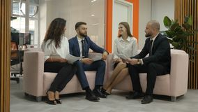 Office workers two young men and two young women stand and discuss an important project of the firm, men shake hands. Girls clap and smile, office, boss, boss stock video footage