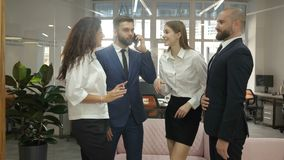 Office workers two young men and two young women are standing and discussing an important project of the firm, an. Emotional discussion of company documents stock footage
