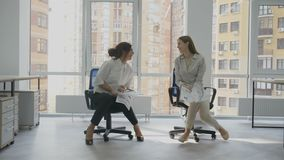 Office workers, two young women sitting on a chair holding documents in hands joyfully looking at each other laughing. And showing class at the same time 4k stock footage