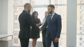 Office workers, two young women and two young men, two men talking and agreeing to each other, two women in the. Background looking at them and smiling 4k stock video footage