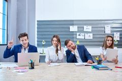 Office workers are working, one of them is sleeping at the desk. Four young office workers of guys and girls in business suits are sitting at the desk in the Royalty Free Stock Photography