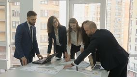 Office workers, a young team of the company, two men and three women discuss the installation documents developed for. The company, as well as documents stock footage