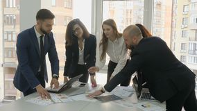 Office workers, a young team of the company, two men and three women discuss the installation documents developed for. The company, as well as the reports stock video