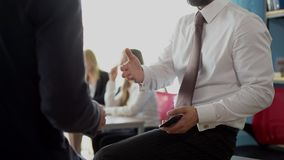 Closed-up view of businessmen having discussion in office. Daily office workflow. Stylish businessmen having discussion in office. Closed-up view stock video