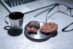 Office working desk with laptop, pen and and glasses and coffee with cookie and sweets. Office working desk, top view with laptop, notepad and coffee with memo Royalty Free Stock Images