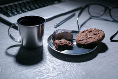 Office working desk with laptop, pen and and glasses and coffee with cookie and sweets. Office working desk, top view with laptop, notepad and coffee with memo Royalty Free Stock Image