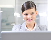 Office Working Typing on a Computer. Young businesswoman smiles while working on a computer. Horizontal shot royalty free stock image