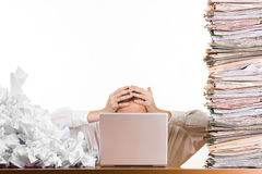 Office Workload. A stressed person holding his head behind a laptop surrounded by a pile of files and papers Royalty Free Stock Image