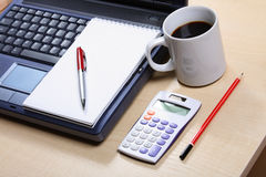 Still life with a blue notebook cup of coffe, calculator, pad, red pen. Office workplace with a blue notebook white calculator notepad, red pencil and white cup Stock Photography