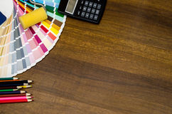 office workplace with brushes, calculate, colorful pencils and color swatches Stock Image