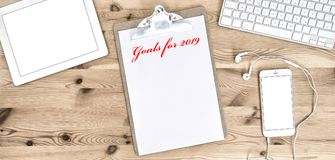 Office Workplace Clipboard Paper New Year goals. Office Workplace with Clipboard, Paper, Keyboard, Pad, Phone, Headphones. New Years goals 2019 Royalty Free Stock Images
