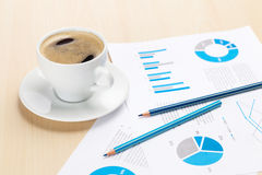 Office workplace with coffee cup and charts Stock Photo