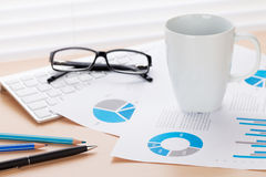 Office workplace with coffee, supplies and reports Royalty Free Stock Photos