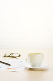 Office workplace with coffee, supplies and reports Stock Photos