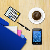 Office  workplace  with  graph and  cup of coffee on wooden table Royalty Free Stock Photo