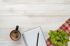 Office workplace with green houseplant on checkered tablecloth, cup of coffee and empty notebook. Royalty Free Stock Images