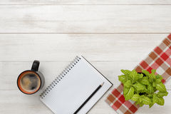 Office workplace with green houseplant on checkered tablecloth, cup of coffee and empty notebook. Royalty Free Stock Photo