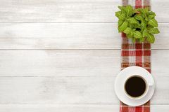 Office workplace with green houseplant on checkered tablecloth, cup of coffee Royalty Free Stock Image