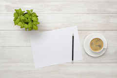Office workplace with green houseplant, cup of coffee, white paper and pencil in top view Royalty Free Stock Photo