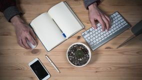 Office workplace with Hands. Laptop, daily planner, glasses and phone on a wooden table. Top View royalty free stock photo