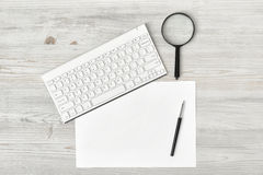 Office workplace with keyboard, pen, white blank paper and magnifier Stock Photography