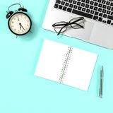 Office workplace Laptop notebook alarm clock blue. Office workplace Laptop, notebook, alarm clock, glasses on blue background Royalty Free Stock Images
