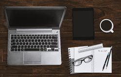 Office workplace with laptop and notebook with eyeglasses and tablet. Top view. royalty free stock photo