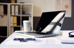 Office workplace with laptop on wood table against the windows Royalty Free Stock Photography