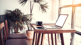 Office workplace with laptop on wood table against the windows.  Stock Image