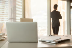 Office workplace with laptops and documents, male silhouette at. Back view of workplace, focus on office desk with laptops and documents, male silhouette at Stock Image