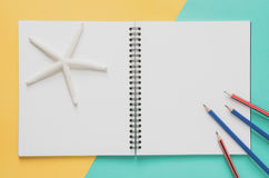 Office workplace minimal concept. Blank notebook with starfishes Royalty Free Stock Image