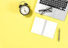 Office workplace minimal flat lay Laptop notebook. Office workplace minimal flat lay. Laptop, notebook, alarm clock, glasses on yellow background Royalty Free Stock Image