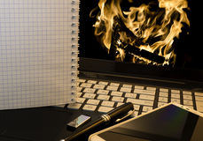 Office workplace with notebook, smart phone, pen, flash drive and wordpad with burning fire Stock Image