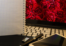 Office workplace with notebook, smart phone, pen, flash drive and wordpad with roses Royalty Free Stock Image