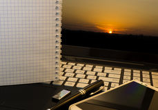 Office workplace with notebook, smart phone, pen, flash drive and wordpad with sunset Stock Images