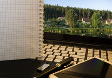 Office workplace with notebook, smart phone, pen, flash drive and wordpad with village nature Stock Photos