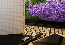 Office workplace with notebook, smart phone, pen, flash drive and wordpad with violet flowers Royalty Free Stock Images