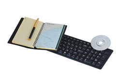 Office workplace with Notepad and keyboard. Notebook with world map and feather pen on a computer keyboard with SD DVD disk Royalty Free Stock Photo