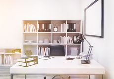Office workplace toning. Creative modern office interior with workplace, bookshelf and blank picture frame. Toned image. Mock up, 3D Rendering Royalty Free Stock Photo
