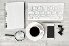 Office workspace with architectural drawing, keyboard, smarthphone, clean book and magnifier on wooden surface in top Stock Image