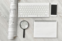 Office workspace with architectural drawing, keyboard, smarthphone, clean book and magnifier on wooden surface in top Royalty Free Stock Image