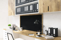 Office workspace with chalkboard side. Side view of office workplace with wooden desk, drawers, shelves with documents and small blank chalkboard on concrete Stock Image