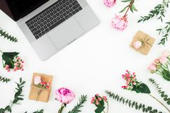Office workspace with laptop and pink flowers on white background. Top view. Flat lay royalty free stock photos